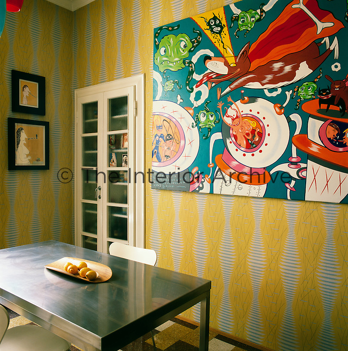 The kitchen has a retro feel with iyellow pattern wallpaper, a stainless steel table and pop art on the walls.