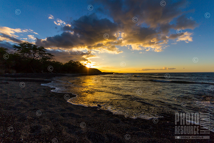 The sun throws its last rays for the day from behind the trees on a beach in Kiholo Bay, Big Island.