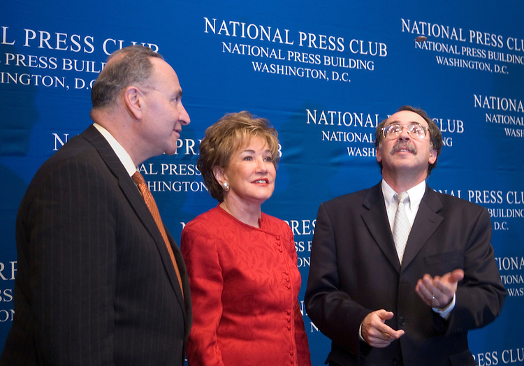 From left, Sen. Chuck Schumer, chairman of the Democratic Senatorial Campaign Committee, and Sen. Elizabeth Dole, chairwoman of the National Republican Senatorial Committee, watch as Jonathan Salant, president National Press Club, flips a coin to see who will speak first at the National Press Club Luncheon on Wednesday, Oct. 25, 2006.