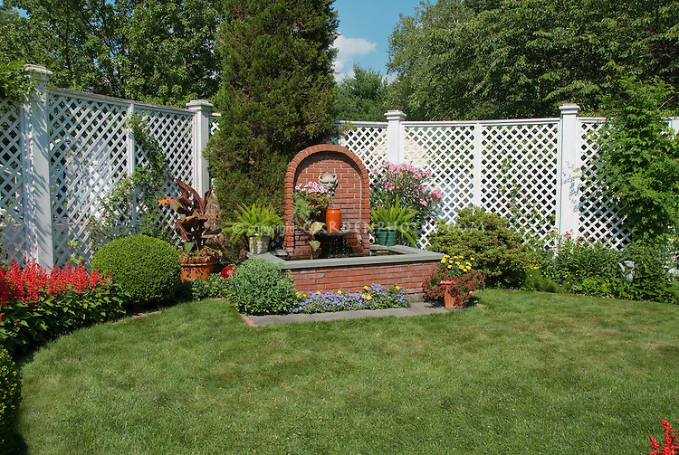Formal water garden fountain of brick in middle of nice lawn grass, white fence, Salvia, container canna