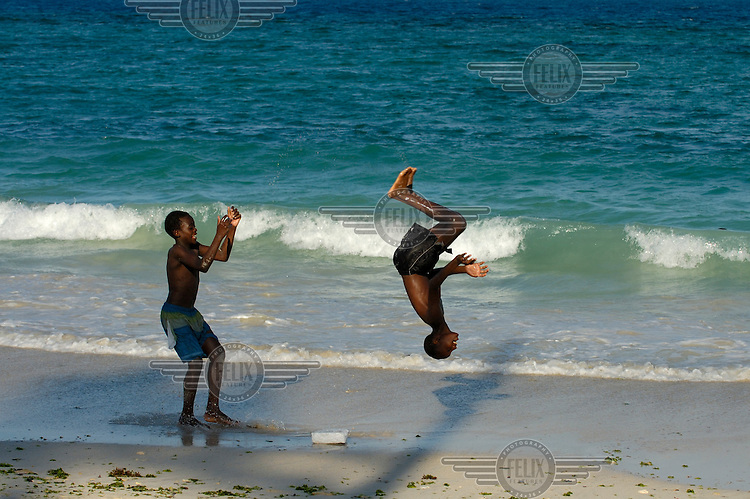 Boys jumping and doing somersaults while playing in the sand on Coco Beach (also known as Oyster Bay Beach).