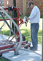 NWA Democrat-Gazette/DAVID GOTTSCHALK Lonnie Luper, with the University of Arkansas Facilities Management Paint Shop, controls Monday, May 13, 2019, the Senior Sand Hog as names are engraved into the sidewalk near the corner of Arkansas Avenue and Dickson Street on campus in Fayetteville. Luper was working with Denny Kaney as they engraved the first 228 of 6000 names that will make up the class of 2018.