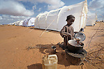 Seven-year old Habiba Hassan Nur, who with her family recently arrived from Somalia, cooks a meal of beans in a new extension of the Dadaab camp in northeastern Kenya. Already the world's world's largest refugee settlement, Dadaab has swelled in recent weeks with tens of thousands of recent arrivals fleeing drought in Somalia. The Lutheran World Federation, a member of the ACT Alliance, is manager of the camp, and in July opened this new extension to begin housing the newest refugees.