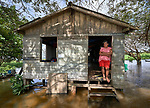 Juscelina Silva Batista, 54, stands in the doorway of her house in the middle of the Amazon River near Santarem, Brazil. She is one of the last holdouts in an area where land is being bought up to build a large port facility.