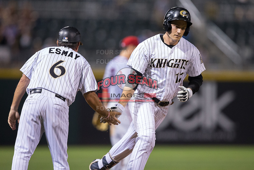 Jason Coats (17) of the Charlotte Knights is congratulated by third base coach Tim Esmay as he rounds the bases after hitting a home run against the Syracuse Chiefs at BB&T BallPark on June 1, 2016 in Charlotte, North Carolina.  The Knights defeated the Chiefs 5-3.  (Brian Westerholt/Four Seam Images)