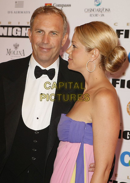 KEVIN COSTNER & CHRISTINA BAUMGARTNER.Muhammad Ali's Celebrity Fight Night XIV held at JW Marriott Desert Ridge Resort & Spa, Phoenix, Arizona, USA, 05 April 2008..half length married husband wife strapless purple pink yellow dress maxi black bow tie tuxedo suit.CAP/ADM/MJT.©MJT/Admedia/Capital Pictures