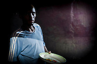 A man stands with an empty plate in a village house in the countryside of Hargeisa, Somaliland, August 9, 2011.
