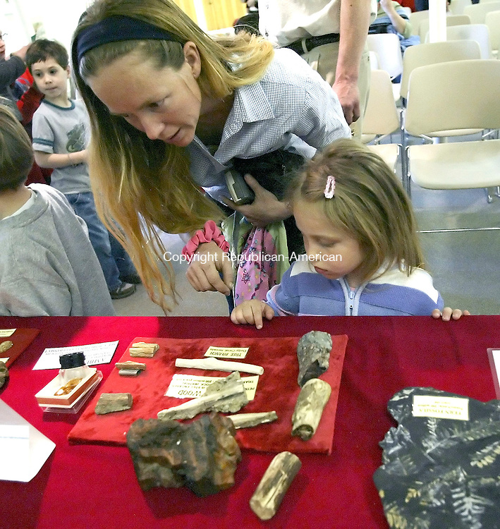 WOODBURY, CT- 16 APRIL 2005-041605JS23--Ameila Frey of Woodbury and her daughter Katie, 4, look over fossils on display following a show by fossil hunter Walt Heinz Saturday at the Woodbury Public Library in Woodbury.    --- Jim Shannon Photo--Woodbury Public Library; Ameila Frey; Woodbury Walt Heinz; Katie Frey are CQ