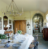 An antique cupboard stands at one end of the dining room and the table is laid with a blue and white dinner service
