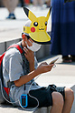 A boy plays ''Pokemon Go'' on his smartphone on one of the hottest days of the summer at Pokemon GO PARK in Yokohama Minatomirai on August 9, 2017, Yokohama, Japan. Hundreds of Pokemon GO app fans gathered at the special Pokemon GO PARK, a 2km area including special PokeStops and PokemonGyms, to collect characters. Minatomirai holds an annual Pokemon event including a parade of 1500 Pikachu through the area and this year has added Pokemon GO attractions. Pokemon GO PARK is open from August 9 to 15. (Photo by Rodrigo Reyes Marin/AFLO)