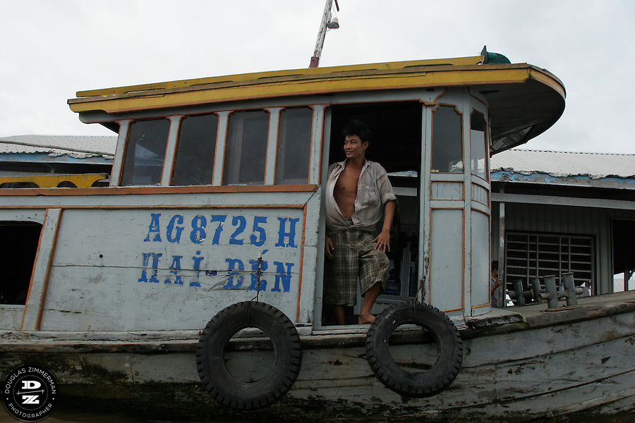A Mekong Delta boat pilot stands next to the helm of his boat on the Bassac River in Chau Doc, Vietnam.  The Mekong Delta has long been the watery  thoroughfare for the many villages that dot the riversides of the delta. Many of the villages have floating markets where people can buy produce and other items from wholesalers.  Photograph by Douglas ZImmerman