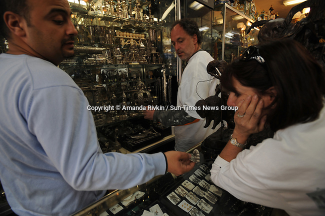 "Efi Naghi, 36, a gemologist at Naghi's on Royal Street in the French Quarter tries to sell ""voluntourists"" silver items Rabbi Steven Lowenstein of Am Shalom synagogue in Glencoe, Illinois, and Bobbi Michaels, 60, from Evanston, Illinois, in New Orleans, Louisiana on March 12, 2008.  The group of ""voluntourists"" from Glencoe, Illinois is traveling to New Orleans to combine traditional tourism with volunteer work in the aftermath of the devastation wrought by Hurrica Katrina in 2005."