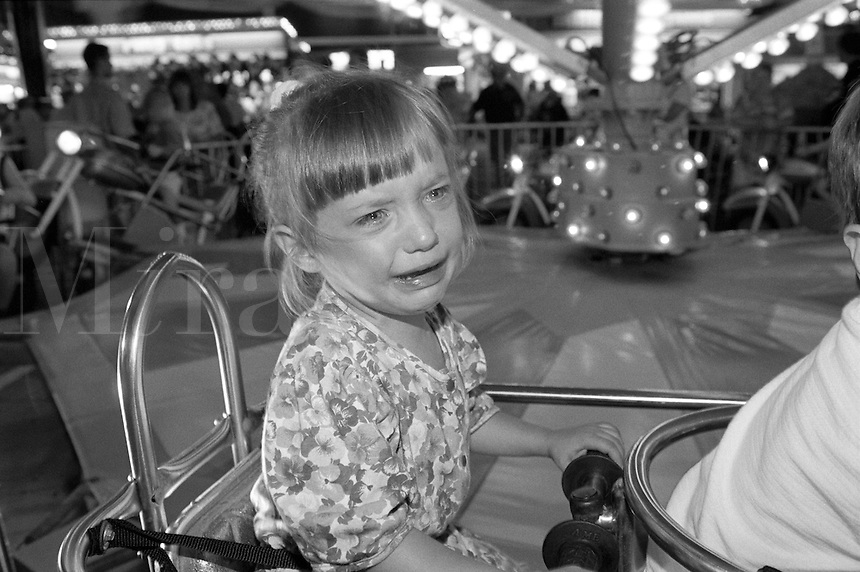 Young girl crying in amusement park. B&W girl crying on amusement ride. White little girl crying on ride.