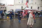Three women supporters crossing the road while sheltering from the rain under umbrellas outside the City Ground, Nottingham before Nottingham Forest take on visitors Ipswich Town in an Npower Championship match. Forest won the match by two goals to nil in front of 22,935 spectators.