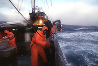 Deckhands work on the F/V Reliance while fishing for crab during a storm in the Bering Sea. (© Karen Ducey Photography)