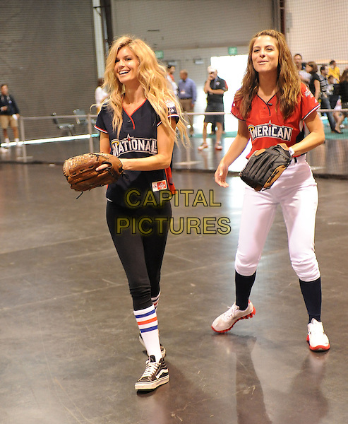 MARISA MILLER & MARIA MENOUNOS .At the MLB All Star Fanfest Batting Practice held at The Anaheim Convention Center , the precursor to The All Star Legends Celebrity Softball game in Anaheim, California, USA..July 11th, 2010.full length red black top baseball mitt glove socks white trousers leggings .CAP/RKE/DVS.©DVS/RockinExposures/Capital Pictures.