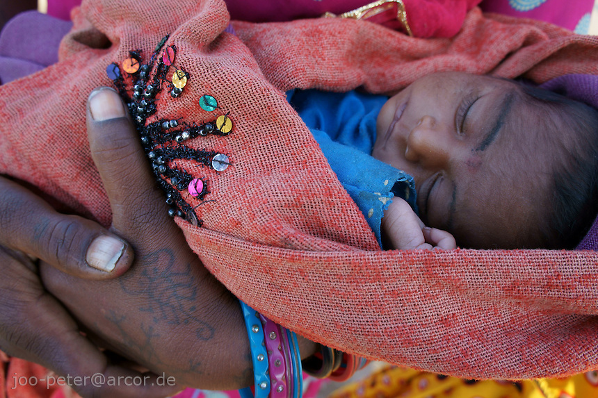 baby born in a small desert  village  in her mothers arm while camel fair  in holy city Pushkar, Rajastan, India