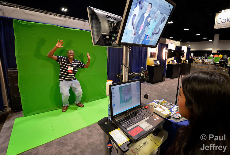 """Using """"green screen"""" technology, Zulema Vega pastes David Muwaya of Uganda in a photo of mission personnel at work in the exhibit hall at the 2012 United Methodist General Conference in Tampa, Florida. Muwaya is a delegate from the East Africa Annual Conference."""