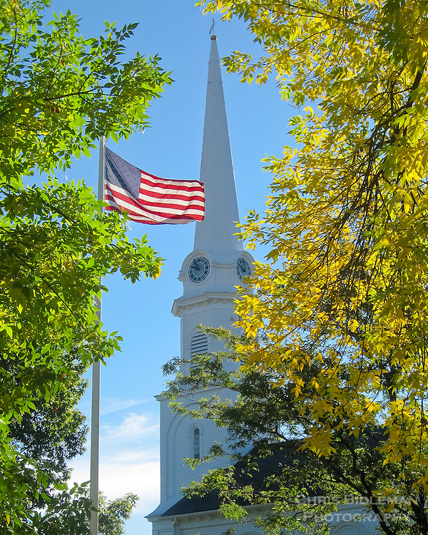 The American Flag waves proudly in between tall trees and is in front of a tall white church steeple in the background during a blue sky day in early Fall in Maine