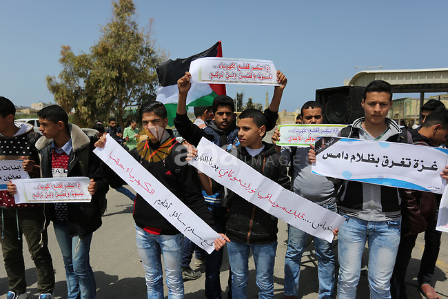 Palestinian school boys hold banners during a protest calling for an end to the power crisis, outside the power plant in the central Gaza Strip April 23, 2017. Photo by Ashraf Amra