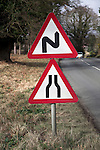 Road ahead with bends and narrowing sign