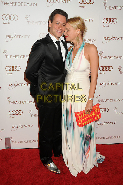 Ioan Gruffudd &  Alice Evans.5th Annual Art Of Elysium Heaven Gala held at Union Station, Los Angeles, California, USA, 14th January 2012..arrivals full length black suit tie silver shoes married husband wife white blue print dress long maxi  red clutch bag .CAP/ADM/BP.©Byron Purvis/AdMedia/Capital Pictures.