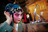 April 15th, 1989, Poyang, Jiangxi Province, China. Traveling opera troupe preparing to perform. Roles in Chinese opera are highly codified. All performers take care of their own make up, clothes and props.