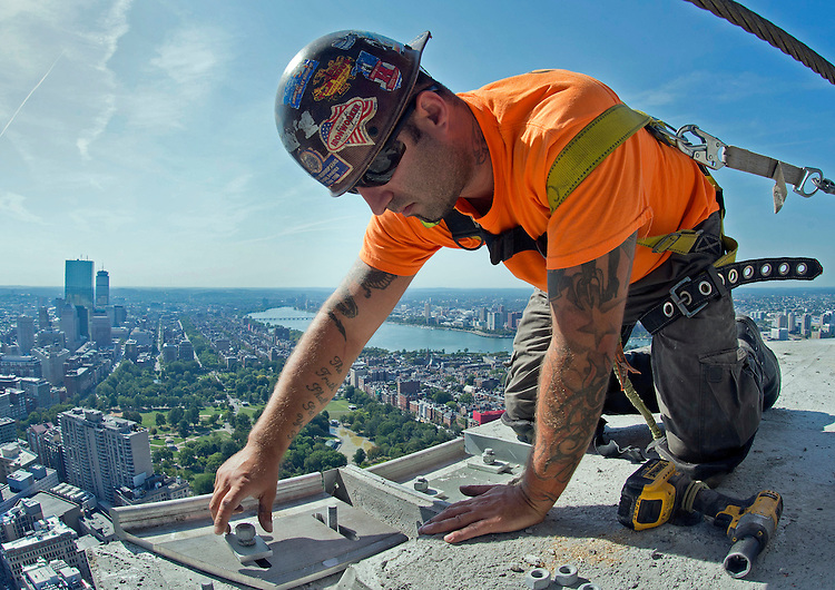 Bobby Zee, a member of Ironworkers Local 7, bolts down a fixture that will help hold the Millennium Tower Boston's glass exterior in place at the 60-story, luxury high-rise skyscraper in Boston's Downtown Crossing on Wednesday, September 16, 2015. Photo by Christopher Evans