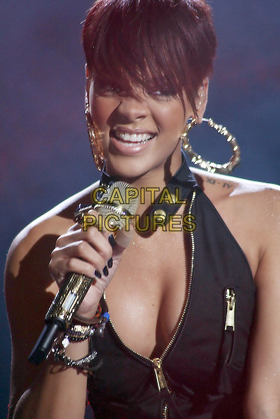 RIHANNA.Rihanna performs in Milan during the Mobile MTV Bang Concert, Milan, Italy, .15 July 2008..music performing live on stage concert gig festival portrait headshot black pantsuit waistcoat halterneck microphone catsuit zips cleavage earrings hoops.CAP/ADM/LIV/AS.©Antonio Sorano/Liverani/Capital PIctures