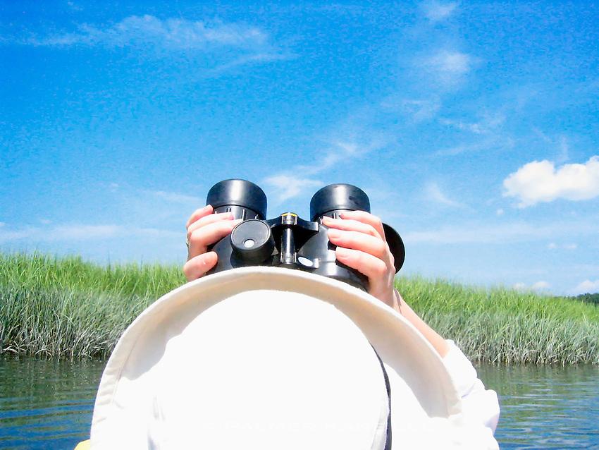 Bird watcher with binoculars in salt marsh