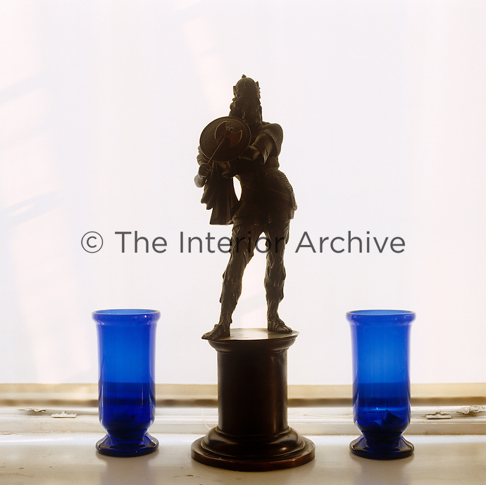 A bronze figurine and two ultramarine glass vases are silhouetted against the diffuse light coming through a simple white roller blind