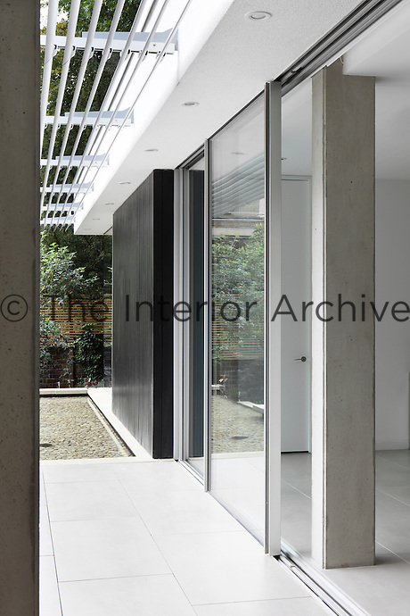 A modern house with a panelled facade and a full height sliding glass door allowing access to a paved terrace.