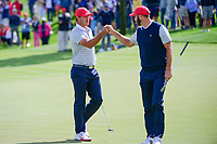 Brooks Koepka (USA) fist bumps Dustin Johnson (USA) after sinking his putt on 3 during round 3 Four-Ball of the 2017 President's Cup, Liberty National Golf Club, Jersey City, New Jersey, USA. 9/30/2017.<br /> Picture: Golffile | Ken Murray<br /> <br /> All photo usage must carry mandatory copyright credit (&copy; Golffile | Ken Murray)