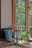 In the kitchen the window frames have been stripped back to the original pine matching the rustic work surface around the butler's sink