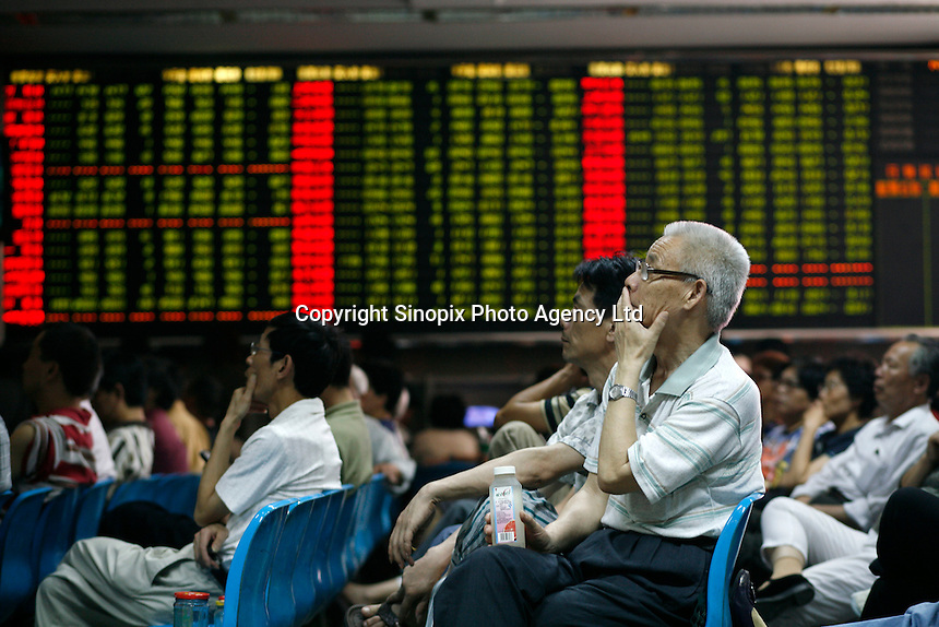 Investors at a securities trading house in Shanghai, China. The Shanghai markets slid nearly 6 per cent on opening today after an announcement of a hike in stamp tax on stock trading from 0.1 percent to 0.3 percent..30 May 2007