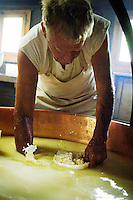 Collecting the curds into the basket moulds from the cauldron...Cowherd and cheesemaker spends 100 days in the summer, high up in the mountains, tending cows and pigs and making cheese at Balisalp and Käserstatt near Meiringen, Switzerland.