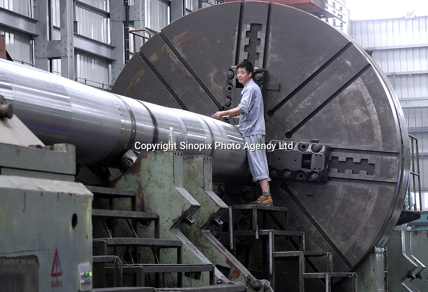A Chinese worker operates on a giant axel at the Hudong Zhonghua Shipbuilding Co., LTD in Shanghai, China. China is the world's third largest shipbuilding nation after South Korea and Japan. While growing international interest in its lower building cost and domestic tanker demand to fulfill the country's hunger for energy is likely to push the country to the top position, the rapidly increasing price of steel has also undercut the industry's profitability..