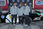 (L-R) Cameron Glenn, Essang Bassey, and Amari Henderson of the Wake Forest Demon Deacons pose for a photo in front of a NASCAR race car in Victory Circle at the Charlotte Motor Speedway on December 26, 2017 in Concord, North Carolina.  (Brian Westerholt/Sports On Film)