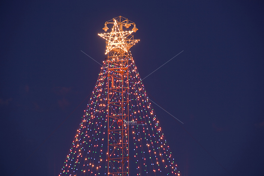 The Zilker Park Christmas Tree has a historic beginning. In the Austin of the 1890's many areas were underdeveloped, hilly, and unpaved. This presented a problem when it came to lighting the streets. In place of normal street lights the City of Austin opted for 31 towers to provide artificial light to the rapidly growing city. Such light towers were already a common form of lighting in many U.S. cities in the late 19th century. The Austin light towers, erected in 1894-1895 by the Fort Wayne Electric Company of Indiana, were approximately 165 feet tall, weighed about 5,000 pounds and used a series of guy wires to keep them vertical. Over the years many of the original 31 towers were lost to construction, errant vehicles and other unfortunate circumstances. Today just 17 of the towers remain standing in Austin. These 17 towers are the last surviving examples of the once popular tower lighting system commonly used throughout the country. They are now designated as official state archeological landmarks and are listed in the National Register of Historic Places.