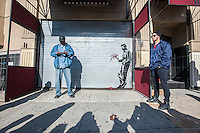 """Street art enthusiasts flock to Larry Flynt's Hustler Club in the Hells Kitchen neighborhood of New York on Thursday, October 24, 2013 to see """"Waiting in vain""""  the twenty-fourth installment of Banksy's graffiti art. The stenciled artwork is on the roll-up gate at the entrance to the gentlemen's club, which has posted security guards outside to protect their new masterpiece.  The elusive street artist is creating works around the city each day during the month of October called """"Better Out Than In"""".  (© Richard B. Levine)"""