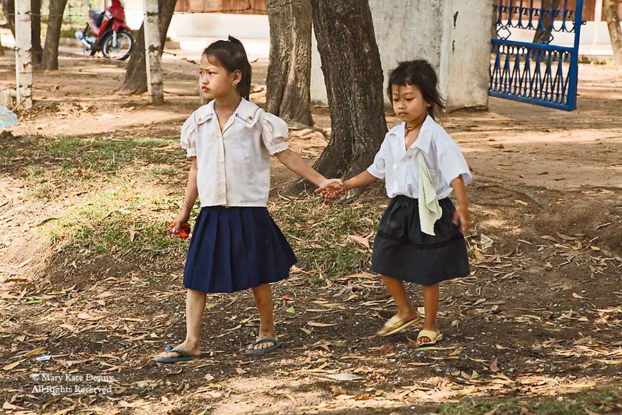 Small Cambodian girls hold hands and walk away from school in uniformsand flip flops