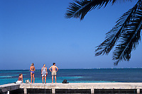 Young tourists relaxing by the sea on Caye Caulker, Belize