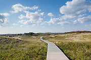 Man walking on boardwalk at Parker River National Wildlife Refuge on Plum Island, Massachusetts during the autumn months. Established in the 1940s, this refuge consists of over 4,000 acres, and because it is located along the Atlantic Flyway it provides a habitat for migratory birds.