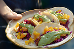 Woman holding a plate of home-made fresh tacos with fish, mango, guacamole and red cabbage filling on corn tortillas Image © MaximImages, License at https://www.maximimages.com