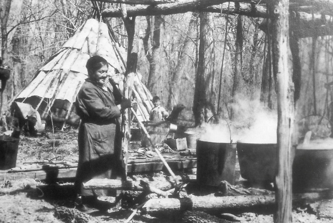 Early 1900's Ojibway (Chippewa) woman making syrup by boiling away the water content over an open fire on the Red Lake Reservation in Minnesota
