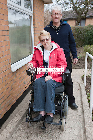 Husband and wife on ramp at adapted home.