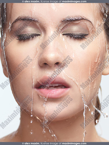Closeup beauty portrait of a woman face with water pouring over it