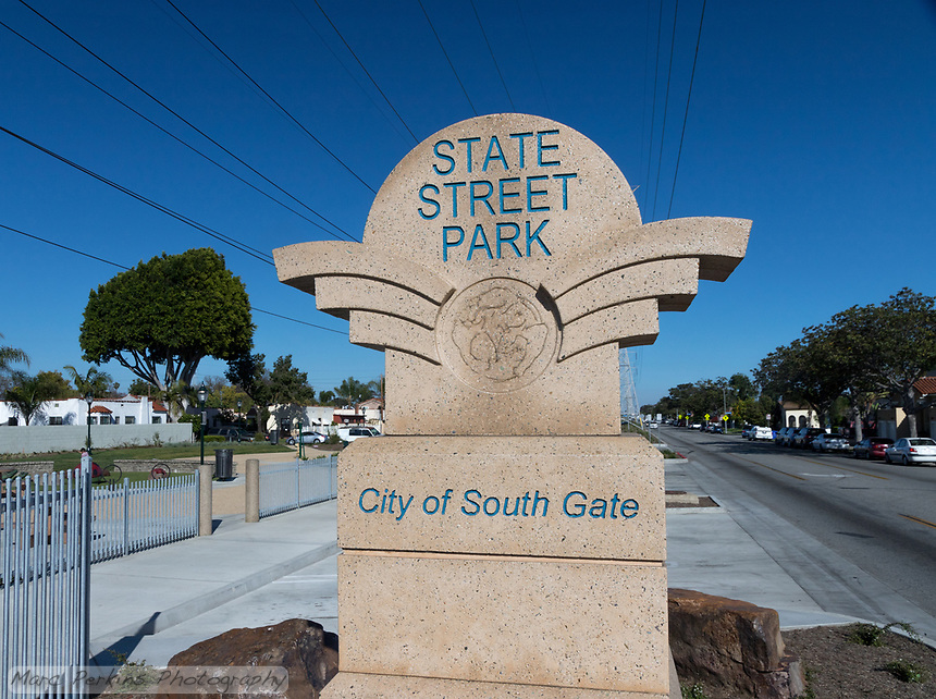 One of the entrance signs to the State Street Park in the City of South Gate, with power lines streaming across the sky and Southern Avenue in the background.