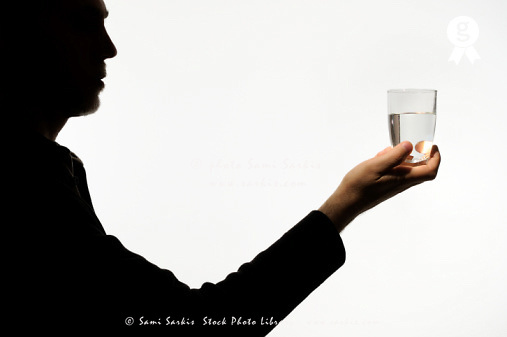 Silhouette of man holding glass of water against white background (Licence this image exclusively with Getty: http://www.gettyimages.com/detail/sb10068346aw-001 )