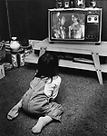 A young Lakota boy watches a western movie on the family television in a public housing project on the Pine Ridge Reservation in South Dakota. Photo by Jim Peppler. Copyright/Jim Peppler/.